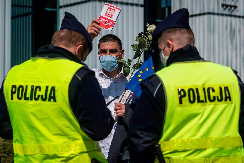 Un homme possède une copie de la constitution polonaise tandis que des policiers vérifient sa carte d'identité après avoir participé à une manifestation à Varsovie, en Pologne, le 30 avril. WOJTEK RADWANSKI / AFP via Getty Images