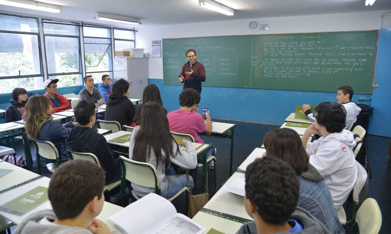 Dans l'image, un enseignant donne des cours à plusieurs élèves de la classe.